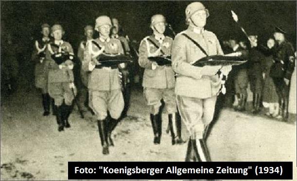 Chef des Stabes der 1. Division, Oberst Hoeppner, der auf einem Kissen den Marschallstab Hindenburgs traegt, gefolgt von sechs Generalstabsoffizieren mit den Ordenskissen des Marschalls.