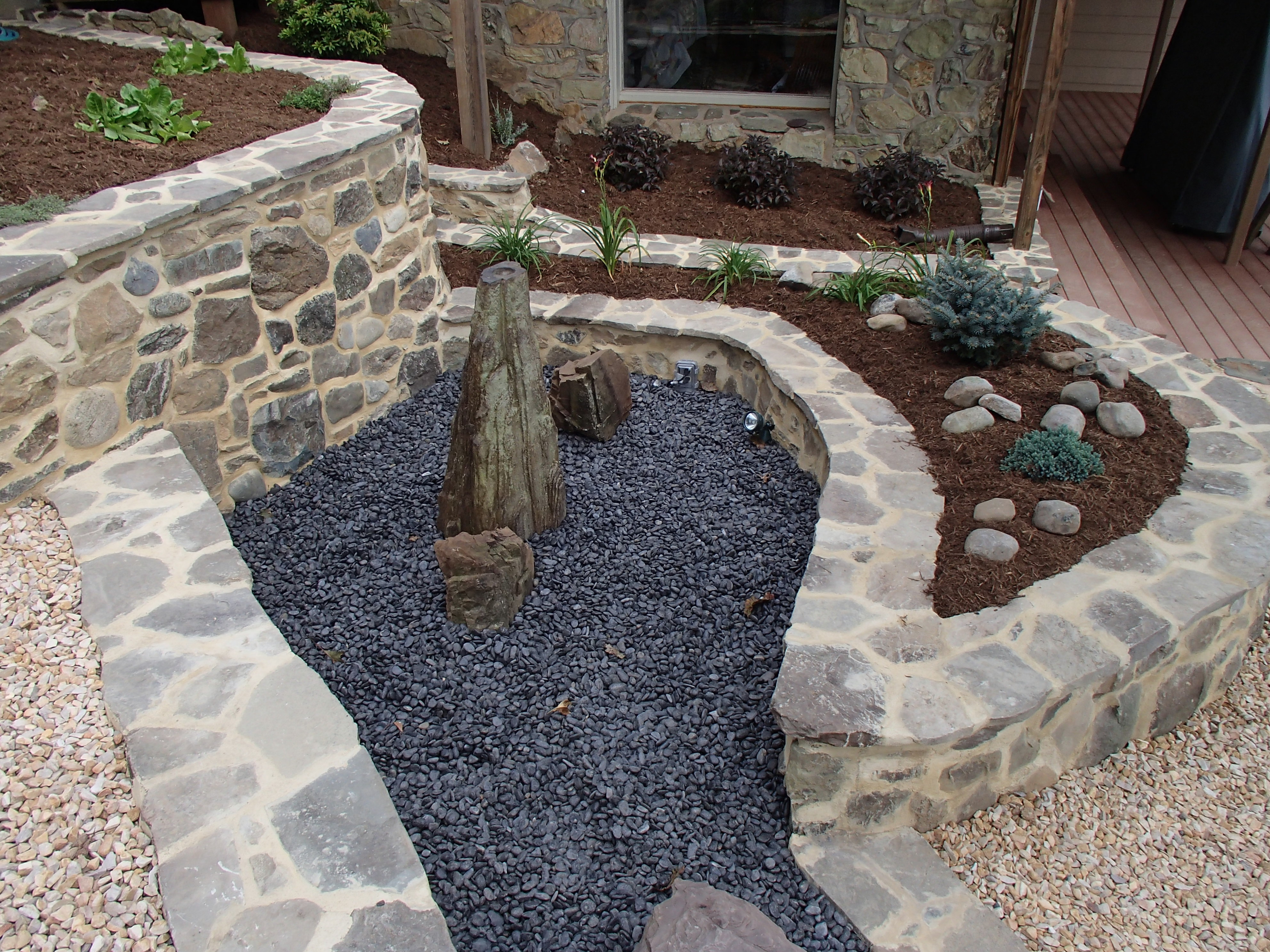 Natural stone retaining walls and pondless water fountain